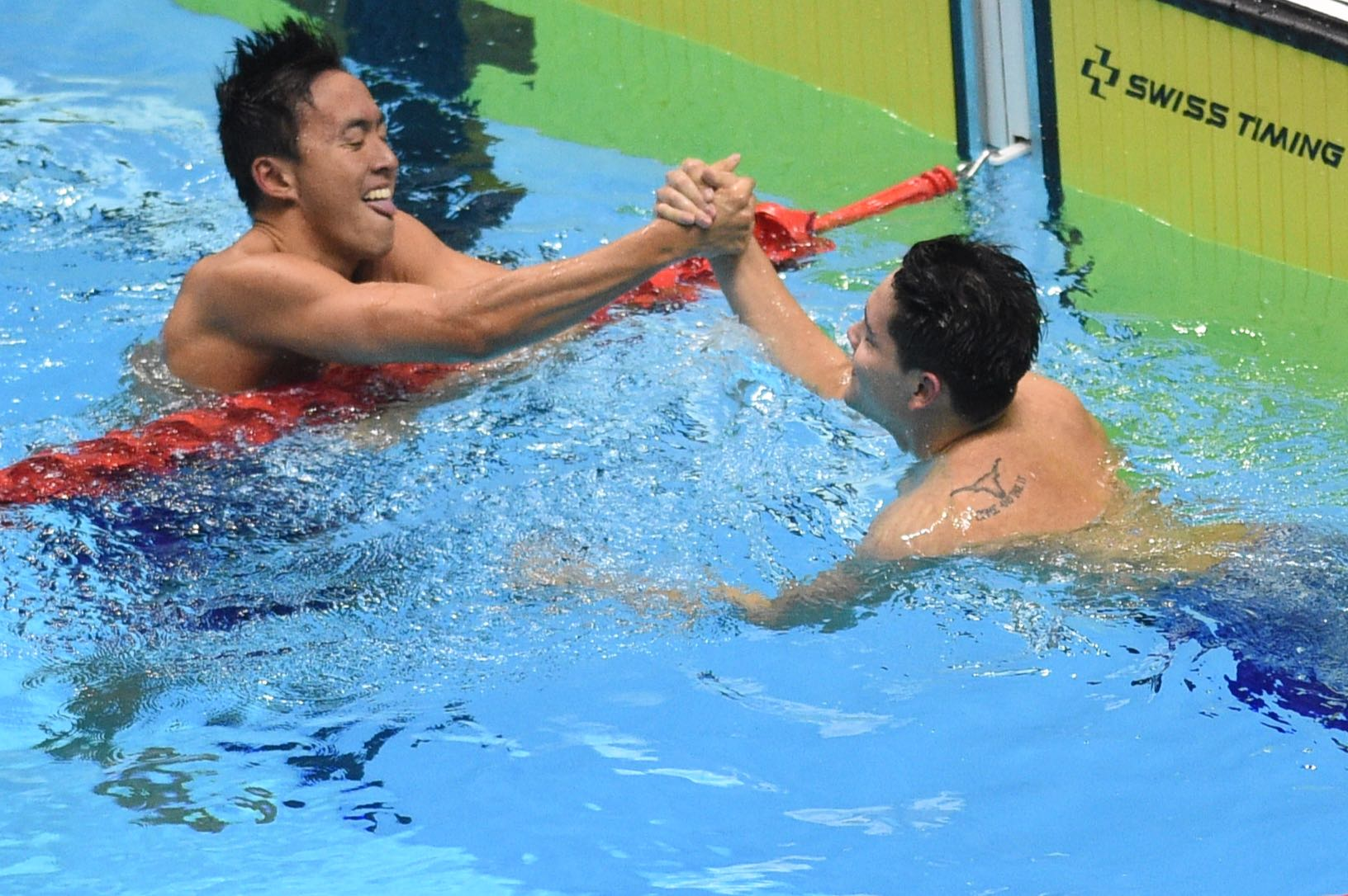 Singapore's Joseph Schooling (R) celebrates with compatriot Zhen Wen (L) after winning the men's 100m swimming butterfly during the SEA Games (Southeast Asian Games) at the Aquatic center in Clark, Capas, Tarlac province, north of Manila on December 6, 2019.