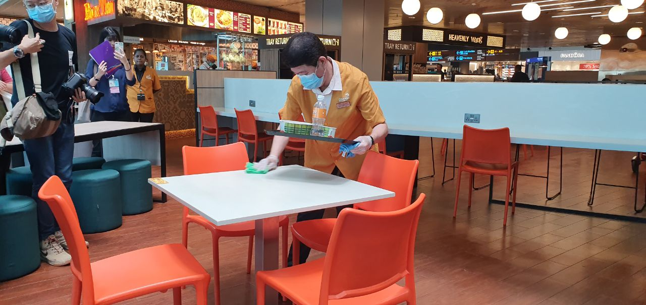 Airport cleaner cleaning cafeteria table