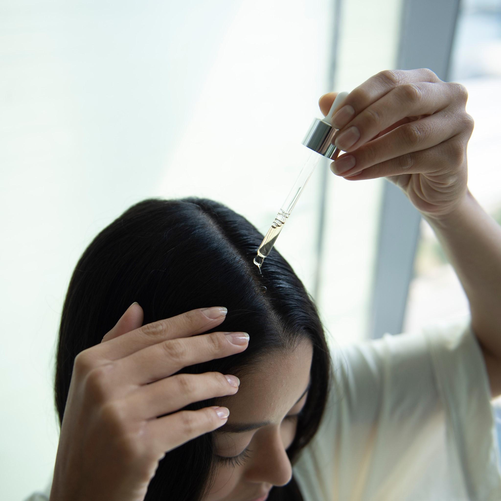 woman applying adv elixir on her hair