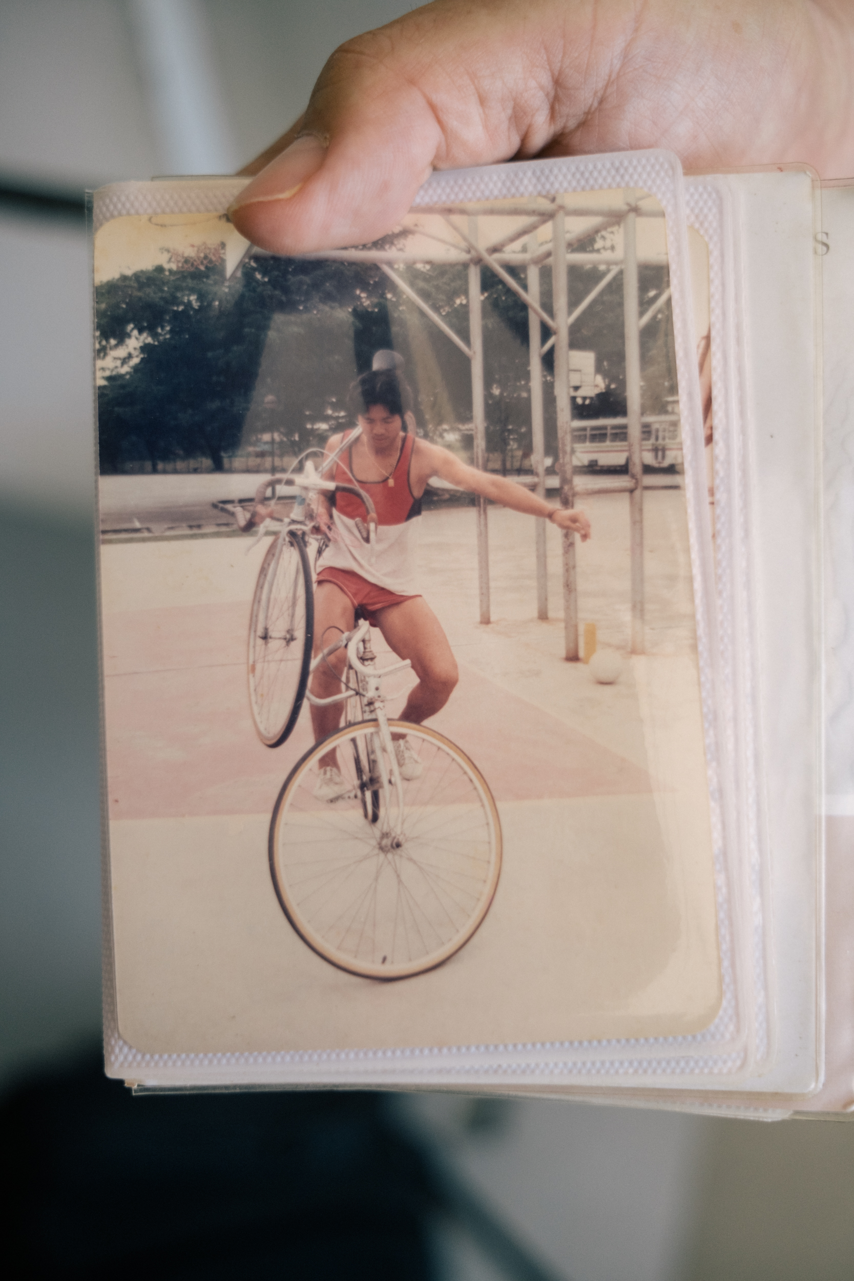 Image of Henry Leong cycling while carrying another bicycle